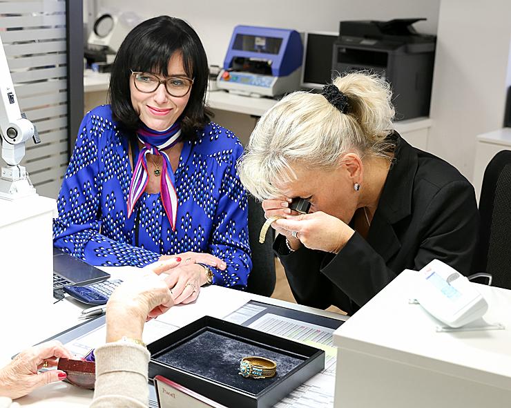 Zwei Mitarbeiterinnen des Expertenzentrums Eppli untersuchen Schmuckstücke und beraten eine Kundin.